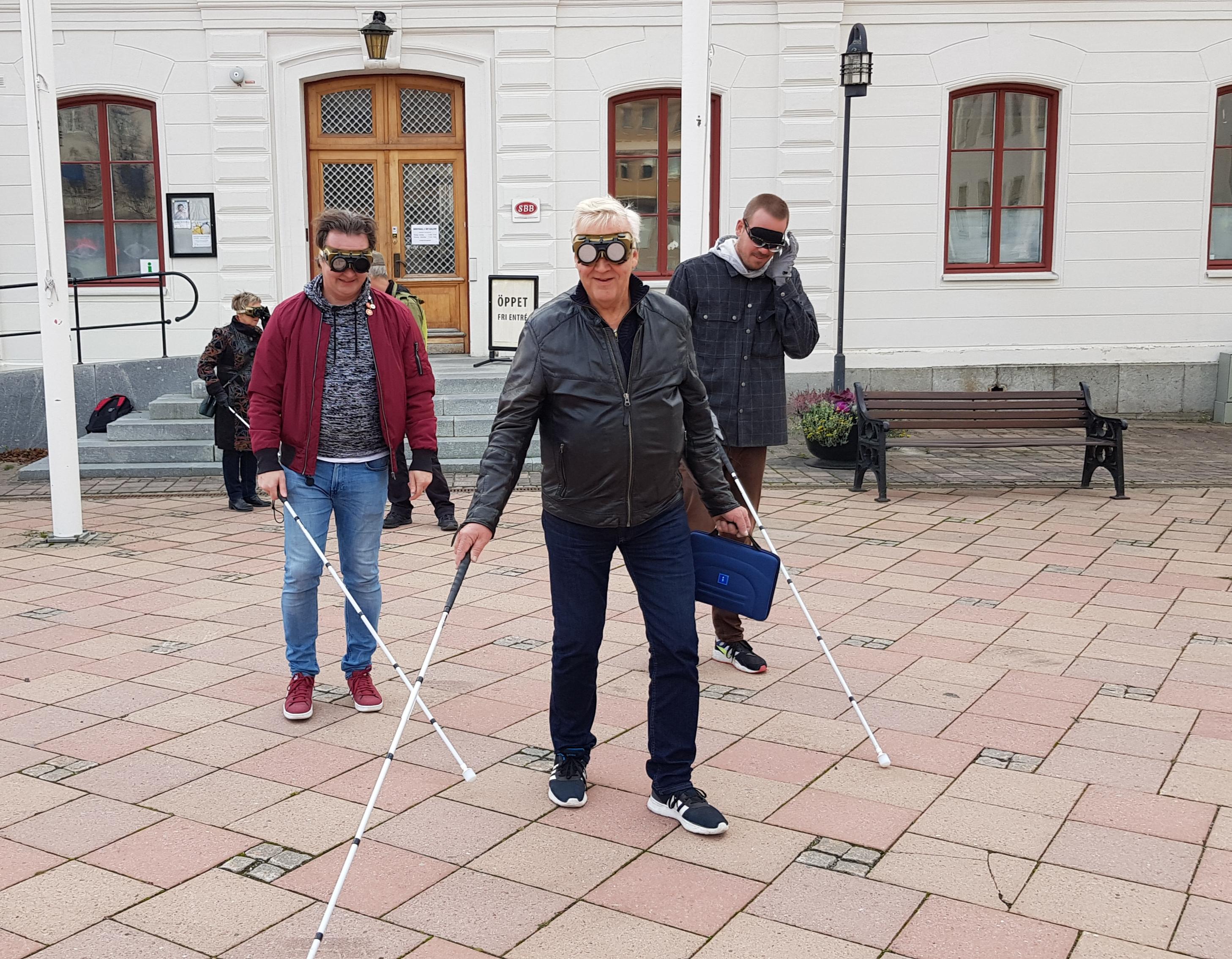 Kommunpolitikerna på promenad på Stora torget i Härnösand med käpp, bindel och glasögon