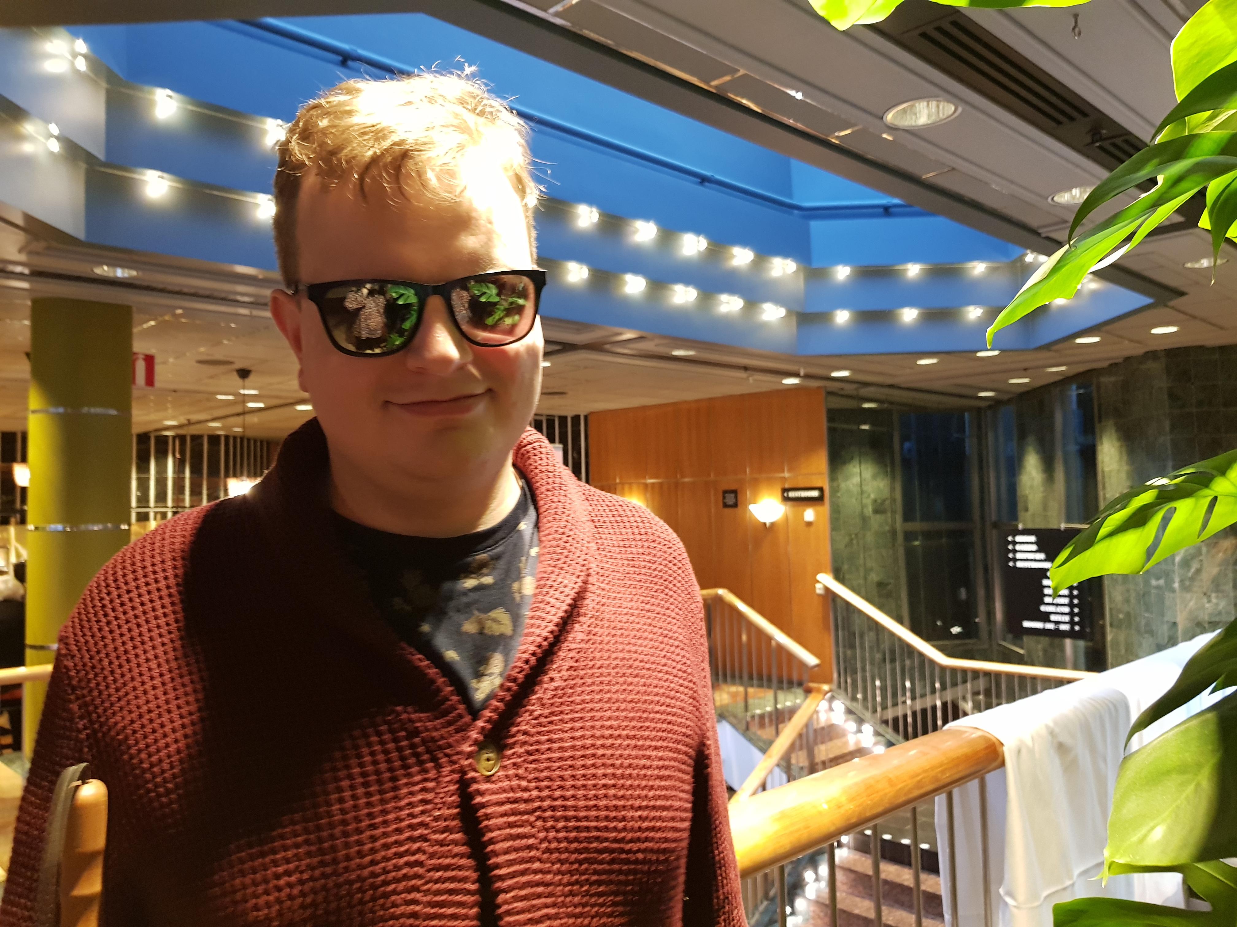 Christoffer har vågit ljust hår och mörka glasögon. Han håller i den vita käppen med ena handen. Han bär en stickad rostfärgad kofta och en svart t-shirt