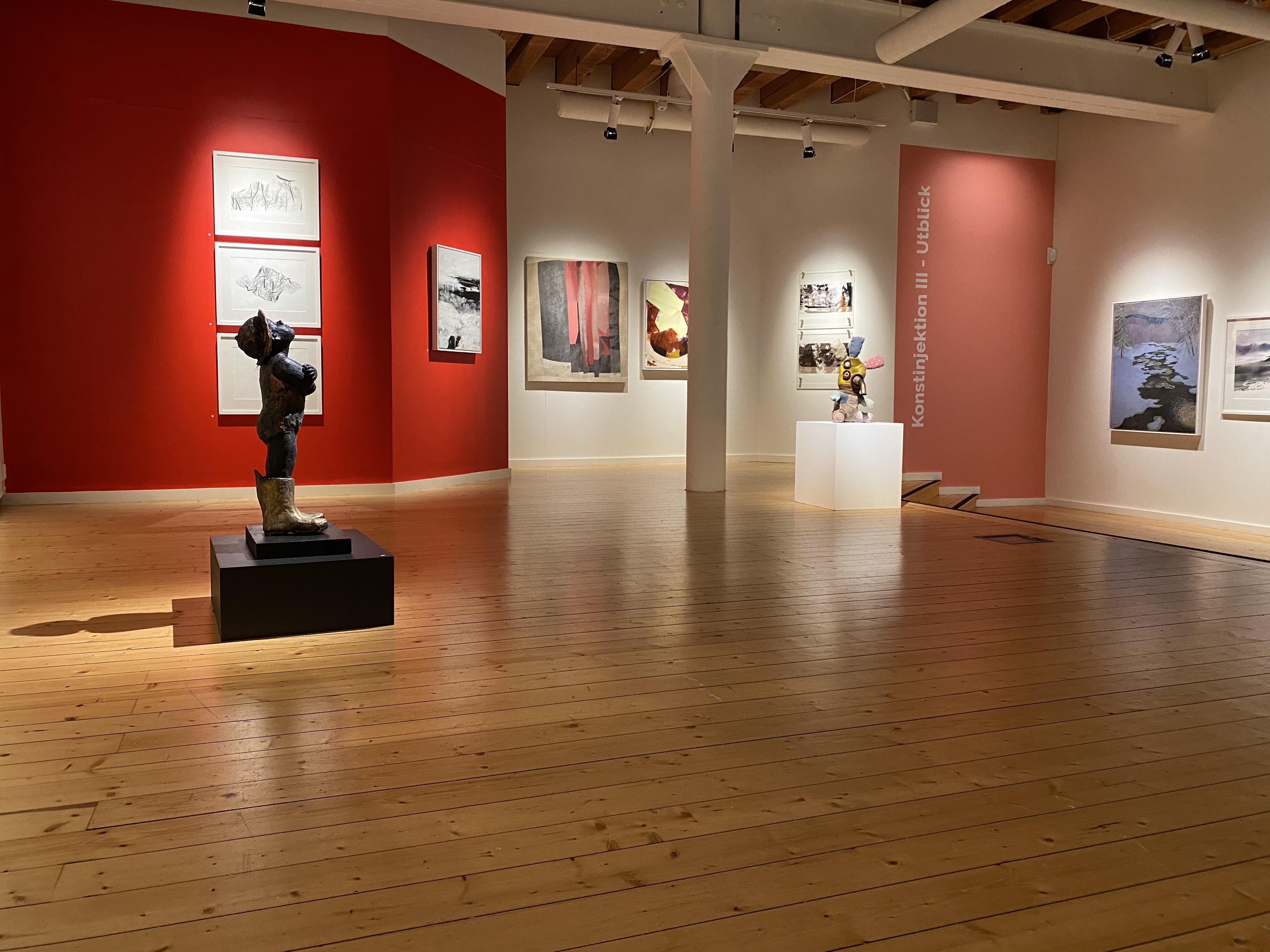 Ett foto från utställningslokalen där skulpturer, tavlor, installationer framhävs av spotlights