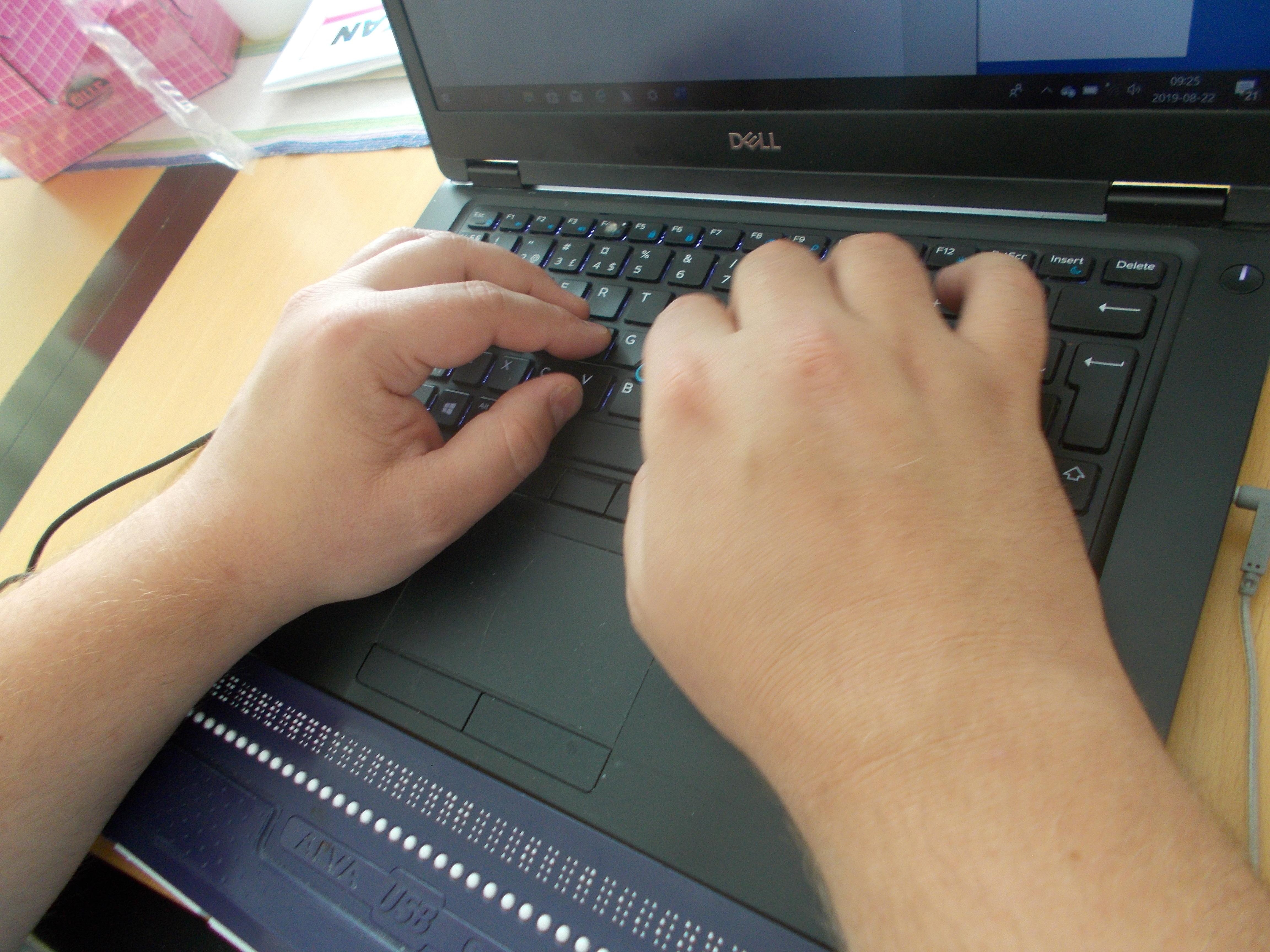 Två händer som läser på punktskriftsdisplayen kopplat till datorn