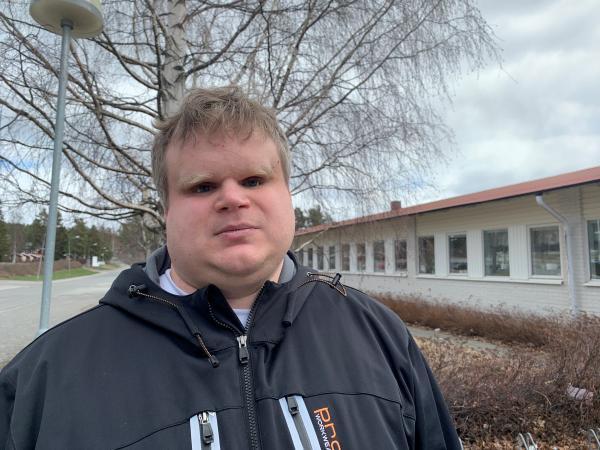 David står utomhus framför en vit byggnad. Han bär en blå sportig vinterjacka på sig