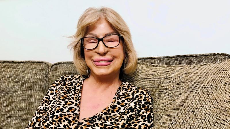 Maria sitter i en soffa. Hon har guldfärgat hår, glasögon och fylliga läppar