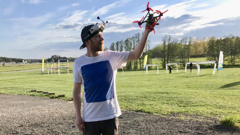 Drönarpiloten står på ett flygfält och håller upp drönaren med ena handen mot himlen