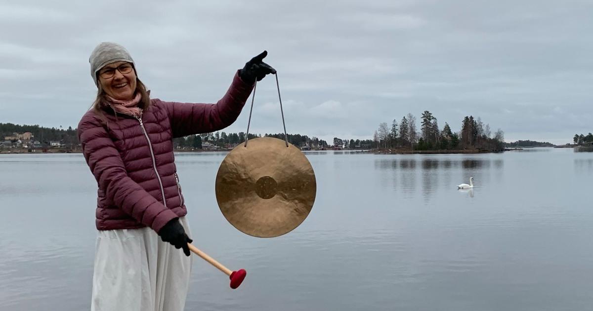 Monica står vid havsbandet i Juniskär med sin mässing gong i ena handen och gongklubban i den andra