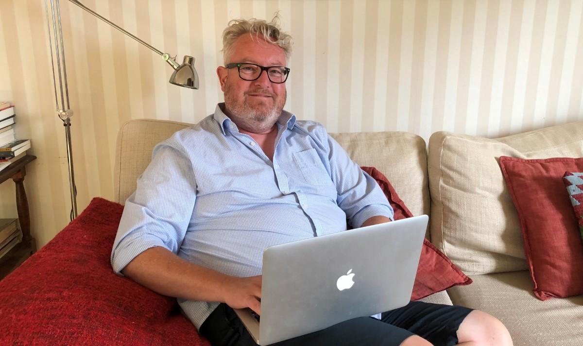 Steven är storvuxen och hargrått hår och glasögon. Han sitter i en beige soffa med datorn i knät
