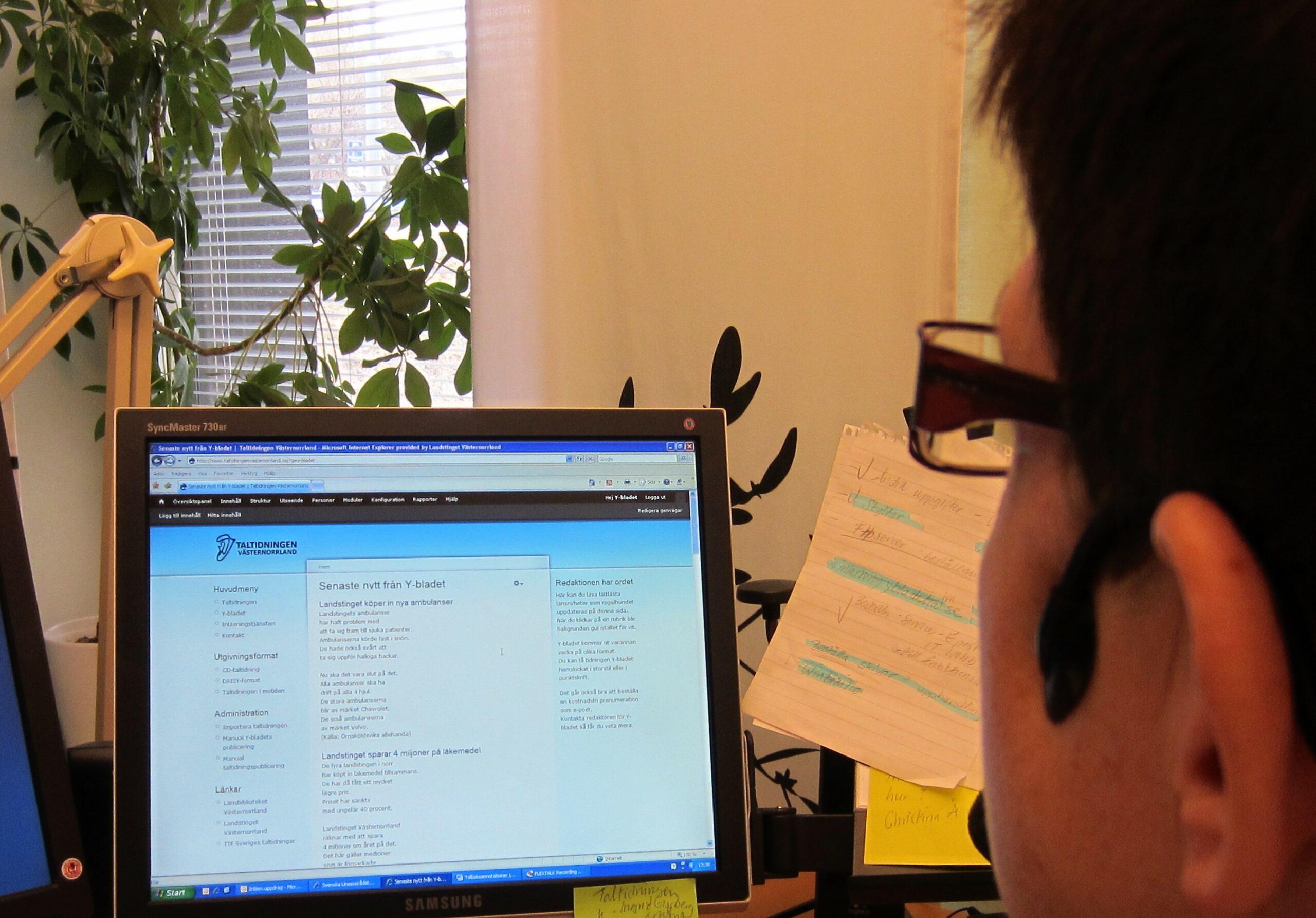 Marie står framför datorn och skriver lättlästa notiser i Y-bladet