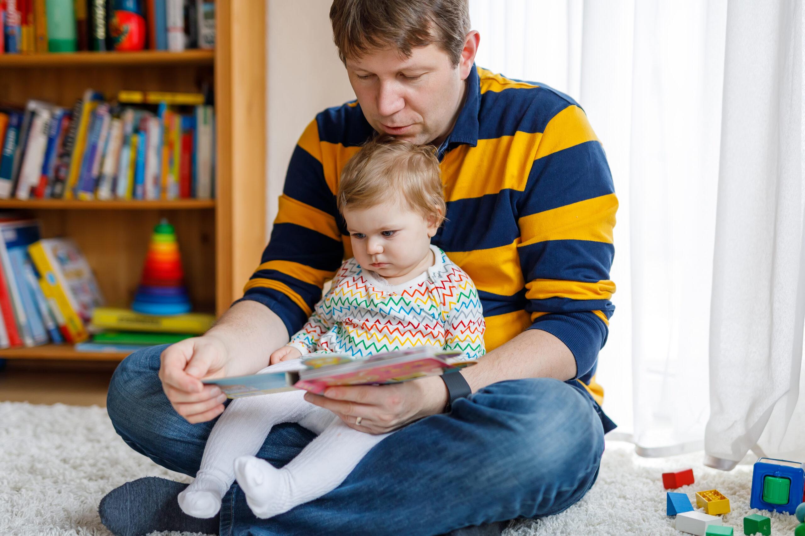 En pappa i randig tröja sitter på golver med sin lilla dotter i knät och läser en bok
