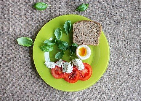 Fiberbröd, ägg, tomater, keso på en grön tallrik