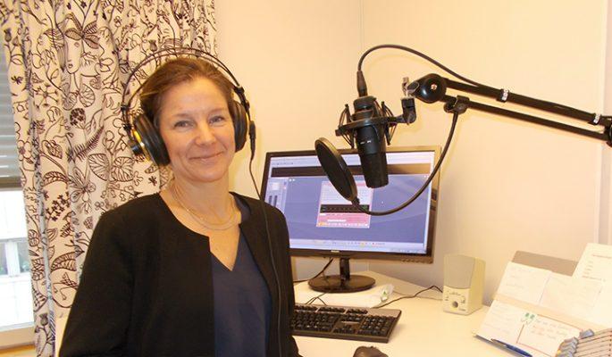 Maria står i ljudstudion med hörlurar på sig framför mikrofonen