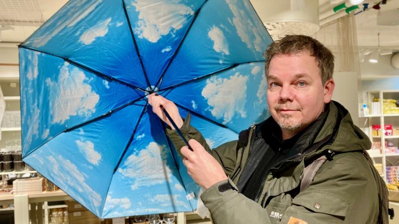 Per Lagergren håller i ett blått paraply. Han har brunt hår och en grön jacka