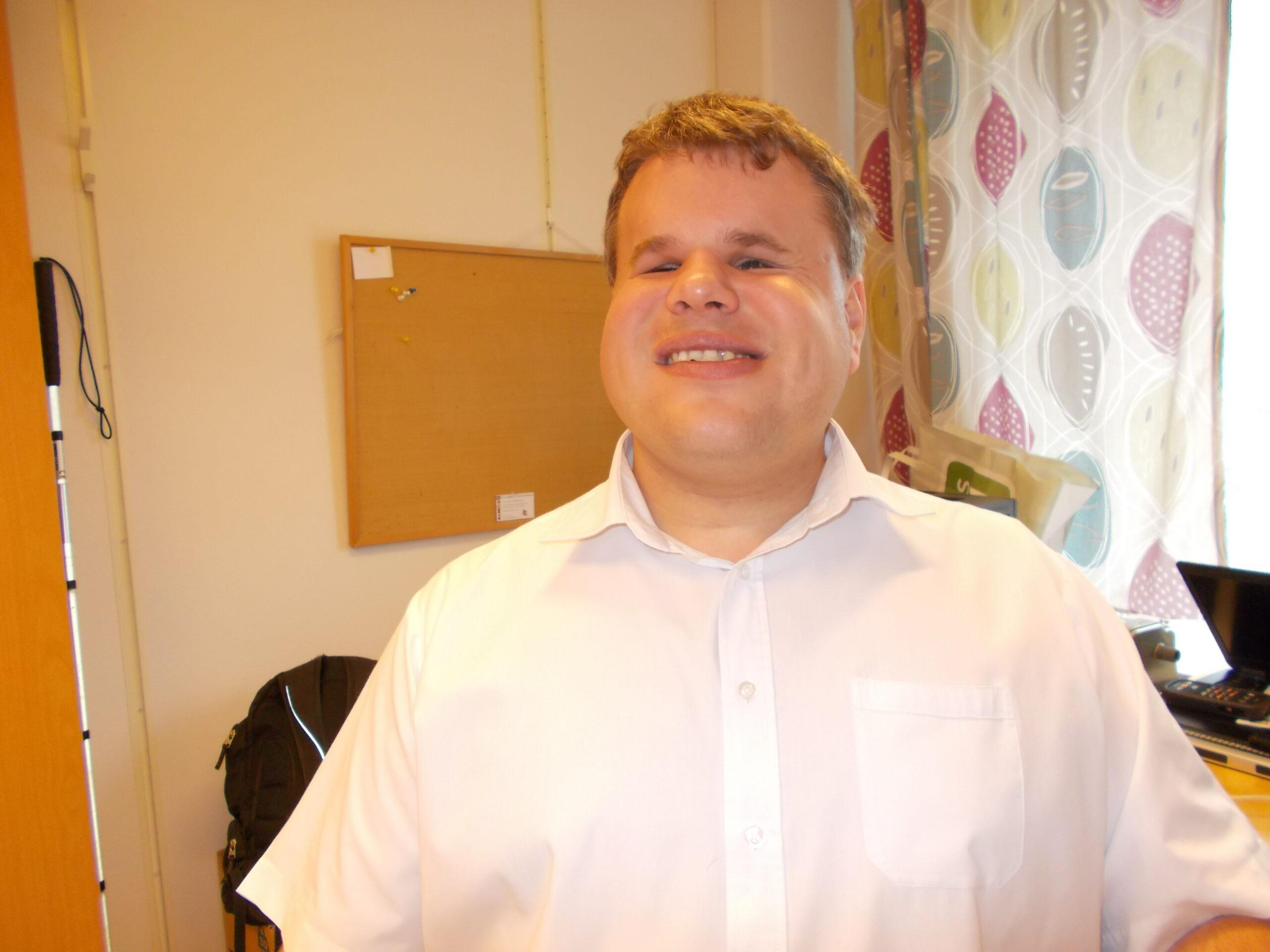 Peter har en ljus skjorta på sig och ler mot kameran