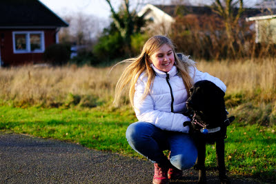 Lily-Ann sitter nedhukad brevid sin svarta ledarhund Maj