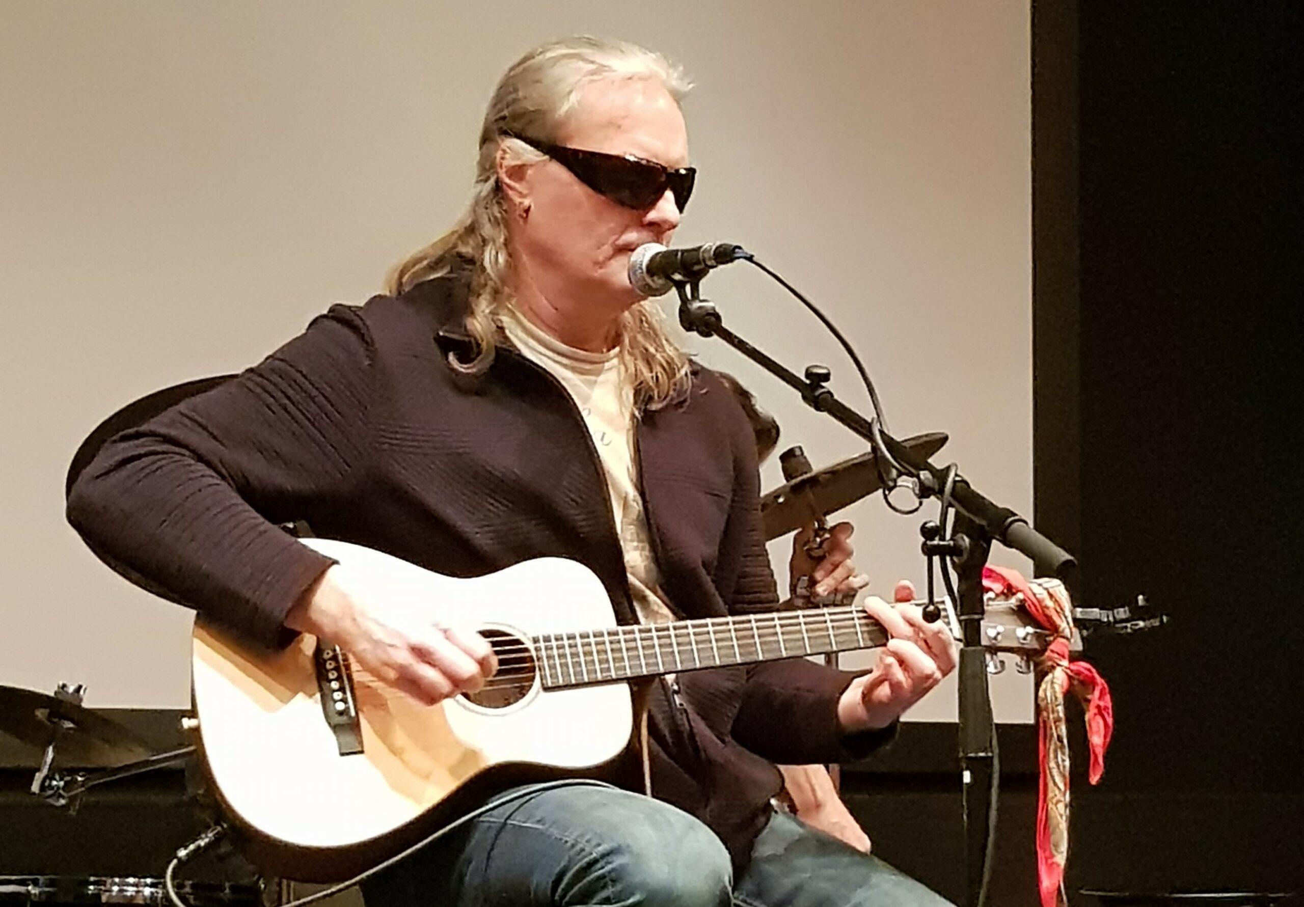 Johan sitter på en barstol på scen och spelar gitarr