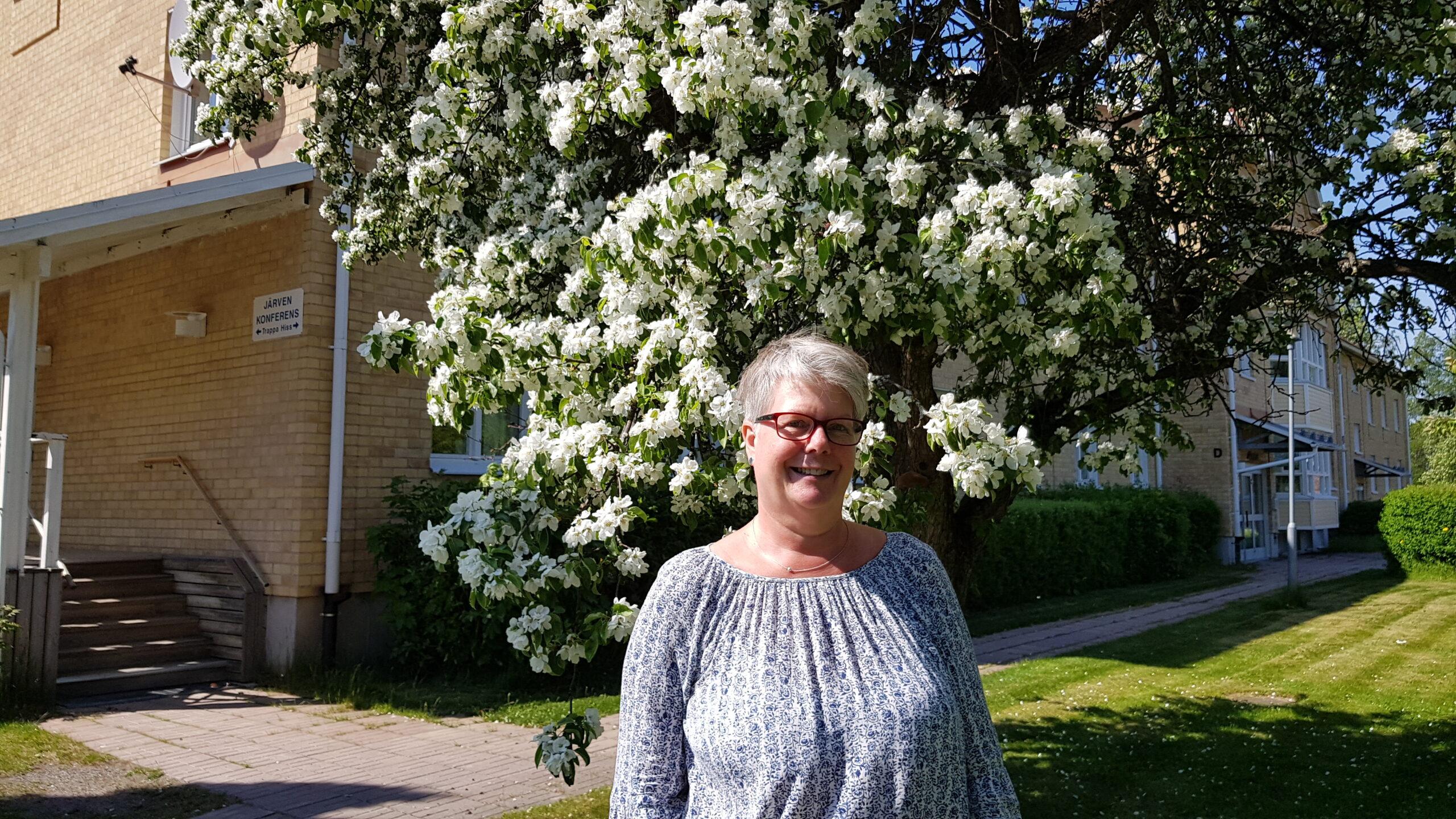 Gunilla har kortklippt grått hår och glasögon. Hon står under ett blommande äppelträd utanför Järvens lokaler vid Härnösands folkhögskola