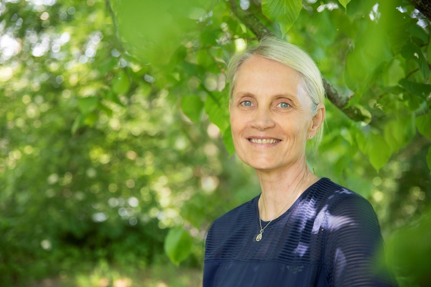 Ulrika har kort blont hår och blå blus. I bakgrunden ett grönt storlövat träd