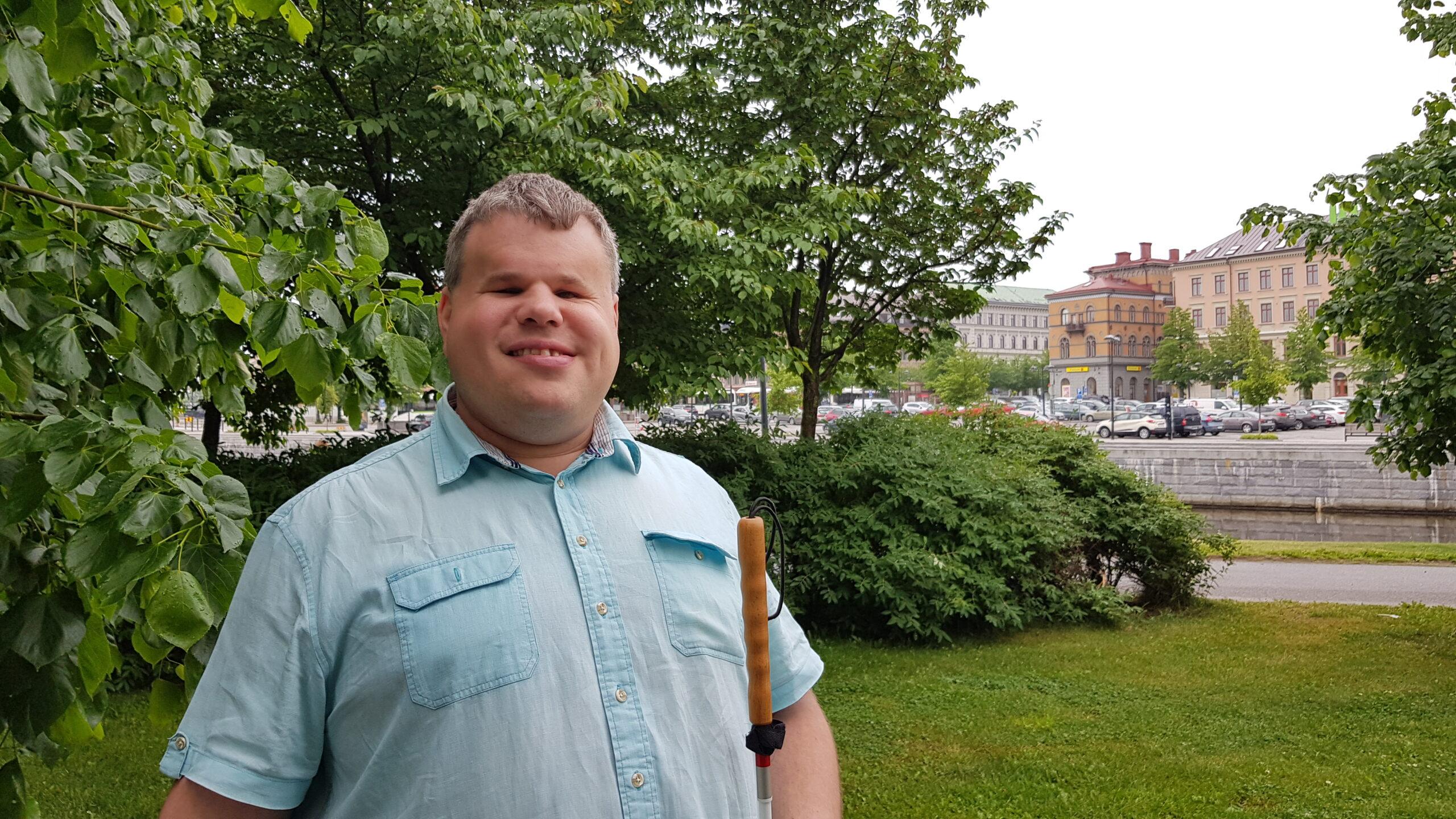 Peter står utomhus i grönskan med Selångersån i bakgrunden. Peter bär en ljusblå skjorta och håller vita käppen i ena handen