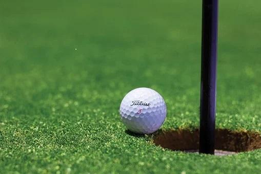 En vit golfboll på Green nära hålet med flaggan i