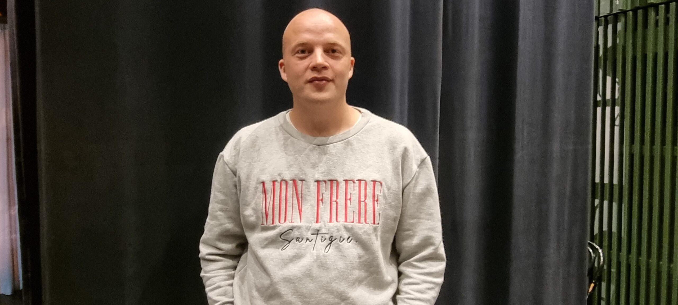 Albin är slätrakad i ansiktet och på huvudet, men i pjäsen bär han peruk. Han har en collegetröja med tryck och svarta jeans