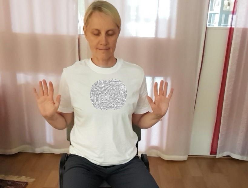 Ulrika sitter med slutna ögon , armarna i vinkel och händerna utåt i höjd med axlarna