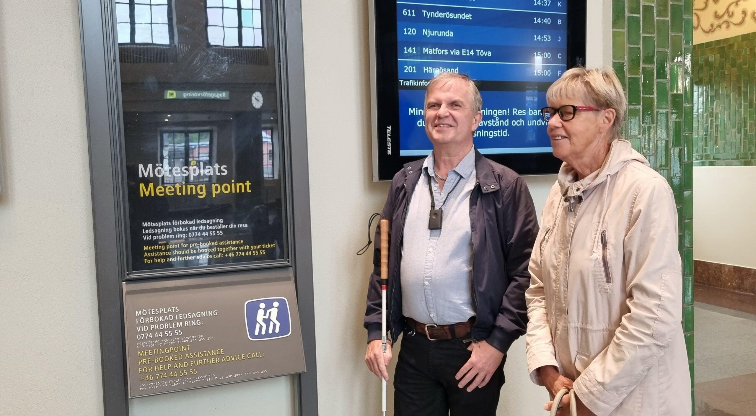 Leif och Marie-Louise framför tavlan vid Mötesplatsen inne i centralstationsbyggnaden
