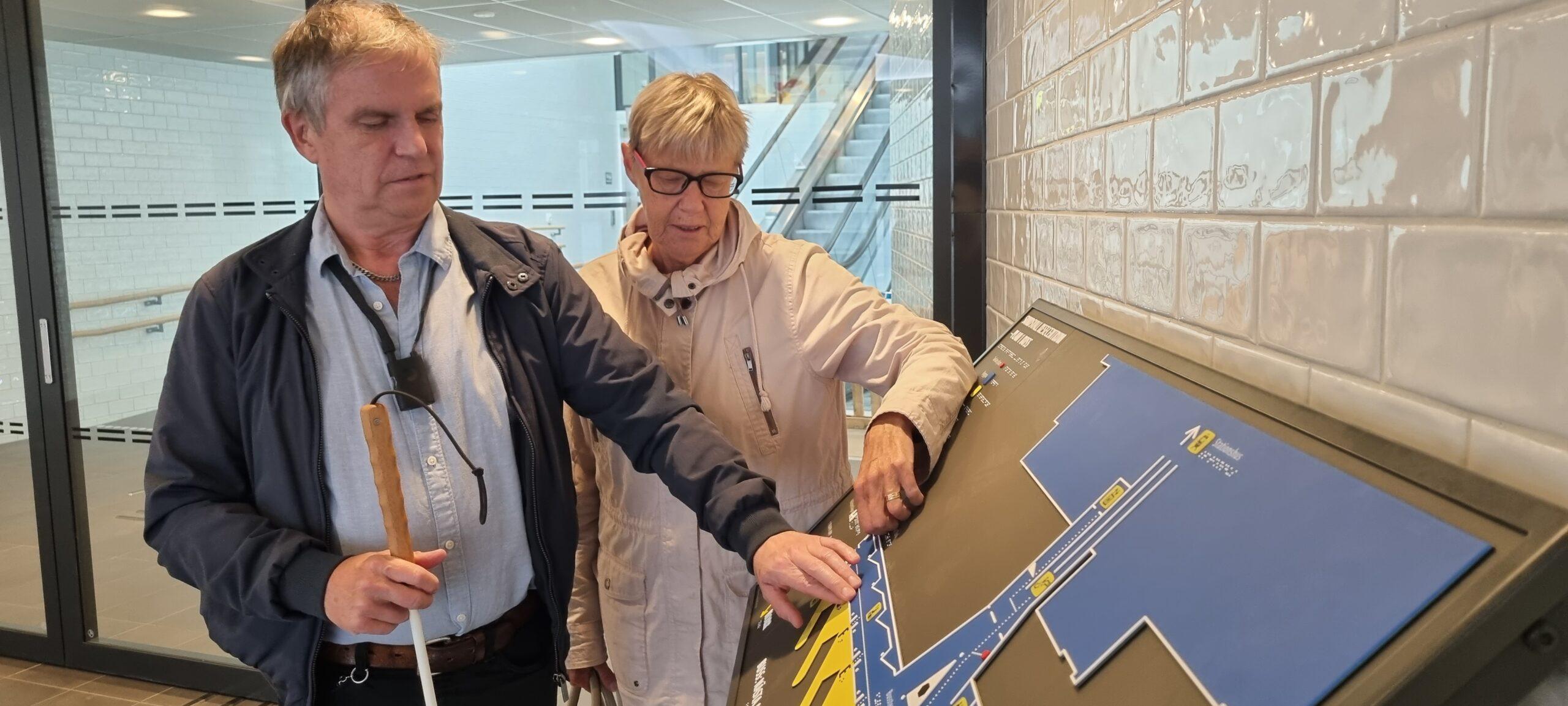 Leif och Marie-Louise känner med fingertopparna på den taktila informationskartan som är gul och blå