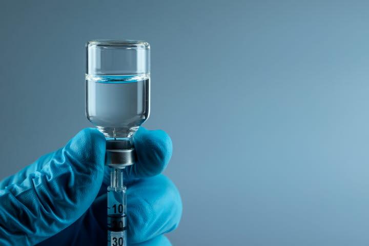 En blå handske håller i ett provrör med vaccin